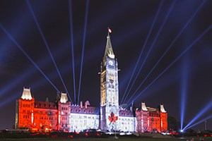 Canadian Parliament Building at night with Canadian flag projected on it