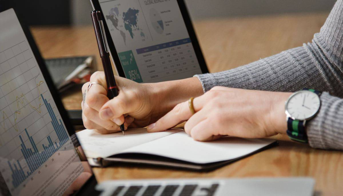 Woman's hand working on financial reports with computers nearby.