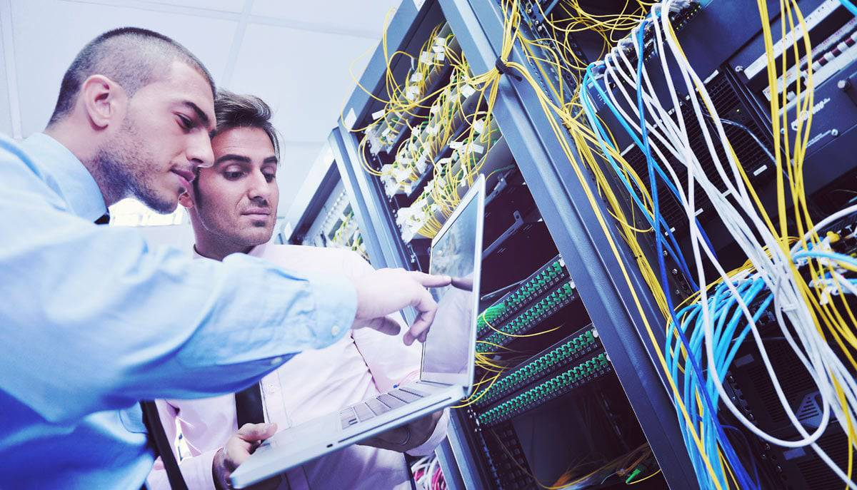Two men looking at equipment tracking software in server room